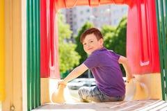幻灯片的愉快的小男孩在儿童操场 免版税库存照片