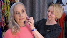 灰发的资深妇女尝试的耳环在辅助部件商店和看反映 帮助的卖主选择羽毛 股票录像