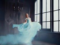 灰姑娘的不可思议的变革到一件豪华礼服的一位美丽的公主里 年轻女人是白肤金发的 免版税库存照片