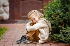 灰棕色的可爱的矮小的卷曲白肤金发的女孩编织了毛线衣微笑 免版税库存照片