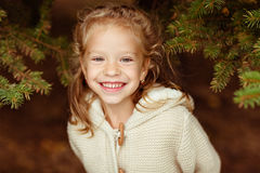 灰棕色的可爱的矮小的卷曲白肤金发的女孩编织了毛线衣微笑 免版税库存图片