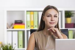 灰棕色的沉思妇女在五颜六色的办公室 库存照片