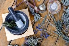 灰浆和杵用干草本、黄铜响铃、水晶和分支五角星形在木背景 免版税图库摄影