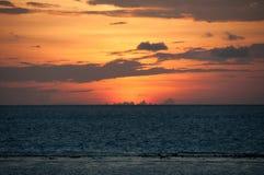 灰色云彩橙色日落天空和条纹在印度洋,马尔代夫的 免版税库存照片