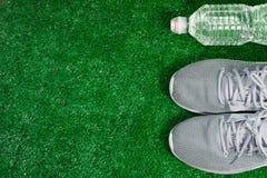 灰色体育跑鞋和瓶在绿草的水 库存图片