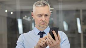 灰色使用智能手机,键入的消息的头发商人 股票录像