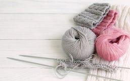 灰色和桃红色编织的羊毛和编织针在白色木背景 顶视图 复制空间 库存照片