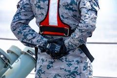 灰色和深蓝数字样式伪装制服的水手拿着携带无线电话用在后面的发怒手 免版税库存图片