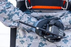 灰色和深蓝数字样式伪装制服的水手拿着携带无线电话用在后面的发怒手 库存照片