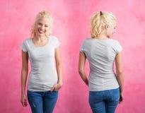 灰色圆的脖子T恤杉的妇女在桃红色背景 免版税库存照片