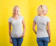 灰色圆的脖子T恤杉的妇女在黄色背景 库存照片
