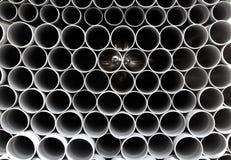 灰色在行堆积的PVC管塑料管道 免版税库存图片