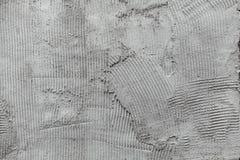 灰色墙壁胶浆膏药梳子表面 免版税图库摄影