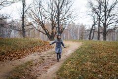 灰色外套和灰色帽子的一逗人喜爱的女孩在橡木的厚实的老橡木附近在日落 免版税库存照片