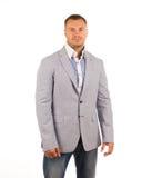 灰色外套和蓝色裤子的俊男 免版税库存图片