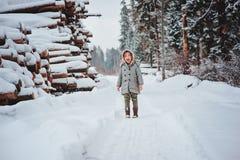 灰色外套的儿童女孩在步行在有砍树的多雪的森林里 免版税图库摄影