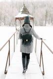 灰色外套的女孩在一座桥梁在冬天 库存照片