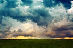 灰色多雨天空和夏天领域 免版税库存照片