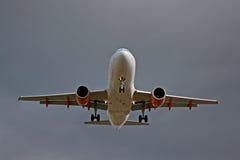 灰色天空的喷气式客机着陆 图库摄影