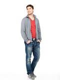 灰色夹克和蓝色牛仔裤的愉快的英俊的人 图库摄影