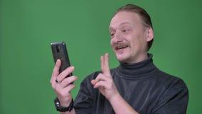 灰色套头衫的白肤金发的领抚恤金者热心地谈话在videochat在绿色背景的智能手机 影视素材