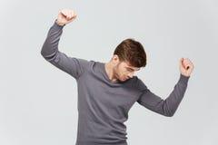 灰色套头衫跳舞的可爱的年轻人 免版税库存照片
