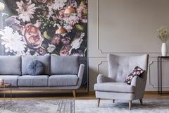 灰色客厅内部的真正的照片与沙发、扶手椅子、墙纸和墙壁造型的 免版税库存照片