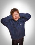 灰色少年儿童男孩报道了他被打开的耳朵尖叫 免版税库存照片