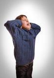 灰色少年男孩孩子报道了他被打开的耳朵尖叫 免版税库存图片