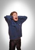 灰色少年男孩婴孩报道了他被打开的耳朵尖叫 库存图片