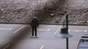 灰色帽子骑马的溜冰板者在停车位,做特技 滑板 股票视频