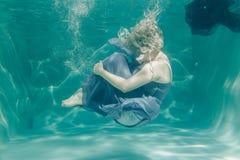 灰色平衡的长的礼服的胖的妇女游泳在水面下她的假日的和享用与放松 免版税图库摄影