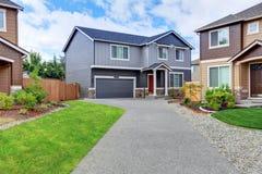 灰色房子外部与深蓝屋顶和长的车道 免版税图库摄影