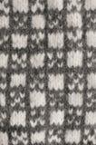灰色手套背景,灰色白色构造了羊毛手套样式,被编织的温暖的羊毛冬天无指的失去指的手套细节 免版税库存照片