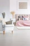 灰色扶手椅子在时髦卧室 免版税库存图片