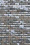 灰色明亮的黑褐色湿被风化的装饰抽象砖墙垂直 库存照片