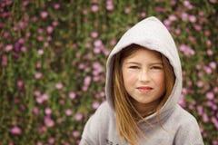 灰色有冠乌鸦的女孩,微笑对照相机,有花卉藤背景 库存图片