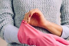 灰色毛线衣和明亮的桃红色修指甲的妇女戴着橡胶手套 免版税图库摄影