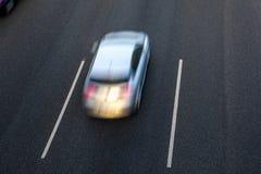 灰色汽车在高速公路快速地运行由中央车道在日落 在其他车道的顶视图和拷贝空间 免版税库存照片
