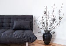 灰色沙发和简单的冬天装饰 免版税库存图片