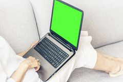 灰色沙发工作的中年妇女在绿色屏幕膝上型计算机,软的焦点 库存照片