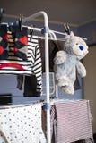灰色玩具熊垂悬干燥在有衣裳的机架 库存照片