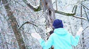 灰色的微笑的白种人女孩编织了手套和帽子 斯诺伊森林在背景中 冬天 雪 免版税库存图片