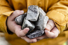 灰色石头在逗人喜爱的小儿童手上 免版税库存图片