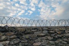 灰色石头墙壁冠上了与铁丝网 库存图片