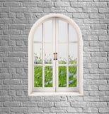 灰色砖墙和白色窗口与绿草和花ov 库存图片