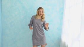 灰色礼服的女孩跳舞对蓝色墙壁在窗口旁边 股票录像
