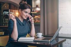 灰色礼服的年轻女商人在咖啡馆的桌上,谈话在手机,当看坐膝上型计算机时屏幕  库存照片