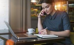 灰色礼服的年轻女实业家在咖啡馆的桌上,谈话坐手机,当采取在笔记本时的笔记 图库摄影