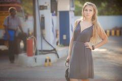 灰色礼服立场的白肤金发的女孩在加油站 免版税库存照片